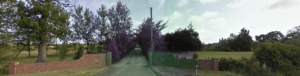 streetview of a driveway surrounded by nature